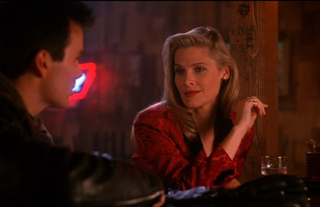 Evelyn, a tall blonde woman we understand to be much older, adopts a flirtatious pose she talks to James Hurley at the bar