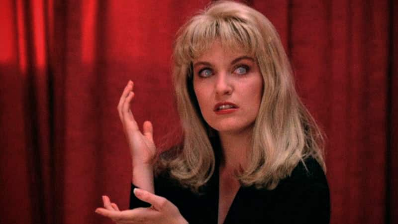 Laura Palmer in the Black Lodge with blue contacts making hand gesture and scary face
