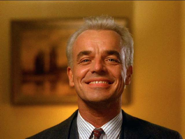 Ray Wise as a white-haired Leland Palmer wearing a devilish grin, gazing into the mirror as we come to learn that he is possessed by BOB