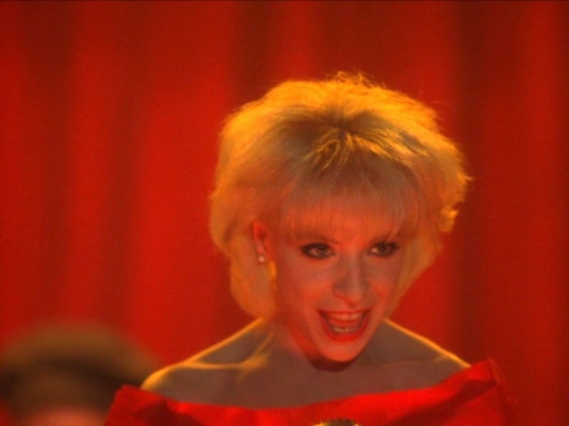 "Julee Cruise in Twin Peaks wearing a red dress against a red curtain singing ""Rockin' Back Inside My Heart"""