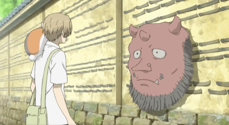 Nyanko-sensei sits perched on Takashi's shoulder as they speak to a red yokai.